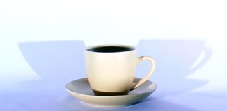 Cup of coffee. Cup and saucer of black coffee; blue shadow in background Royalty Free Stock Photos