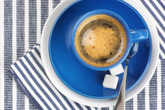 Cup of coffee. Blue cup of coffee on blue striped tablecloth Stock Photography