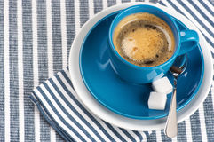 Cup of coffee. Blue cup of coffee on blue striped tablecloth Royalty Free Stock Photos