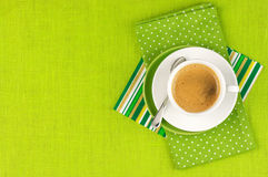 Cup of coffee. White cup of coffee on green linen. Top view Royalty Free Stock Photo