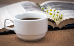 A cup of coffee. A cup of coffee with flowers on a book Royalty Free Stock Photos