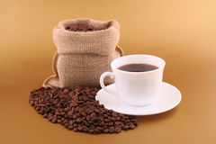 Cup of coffee. White cup of coffee, coffee grains and coffee canvas bag on gold background Stock Photos