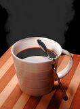 Cup of coffee. Cup of fresh black steeming coffee on wood board ,black background Stock Photography