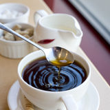 Cup of coffee. Cup of black coffee with a spoon dripping and making ripples Royalty Free Stock Photography