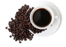 The cup of coffee. In coffee beans isolated at the white background Royalty Free Stock Images