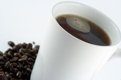 Cup of Coffee. Steaming Coffee Surrounded by Beans Royalty Free Stock Photos