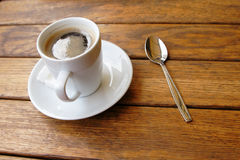A cup of coffee. And teaspoon on the wooden table in cafe Royalty Free Stock Photo