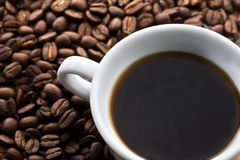 Cup of coffee. A cup of coffee sitting on coffee bean Stock Image