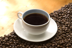 Cup of coffee. A cup of coffee sitting on coffee beans Stock Photography