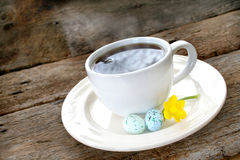 Coffee with Easter eggs. Cup of steaming coffee with small Easter eggs and daffodil on old wooden background Stock Images