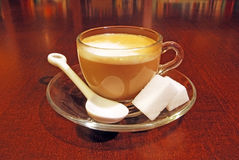 Cup of coffee. In glass cup with two sugar lumps on saucer Royalty Free Stock Photography
