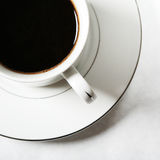 Cup of coffee. White cup of black coffee in the morning light Stock Images