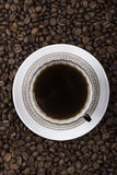 Cup of coffee against beans background closeup royalty free stock image
