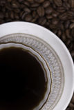 Cup of coffee against beans background closeup. Cup of coffee on beans background close up Royalty Free Stock Image