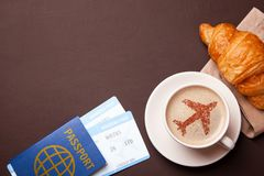 Cup of coffee with an airplane on the foam. I like to break coffee with croissant in flight. Paspor and ticket with smrtrfonom Royalty Free Stock Images