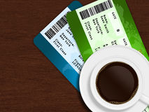 Cup of coffee with airplane tickets lying on wooden table Royalty Free Stock Image