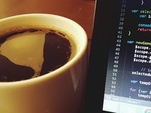 Cup of coffee and AngularJS. A full cup of coffee next to a laptop showing AngularJS source code Stock Photos