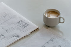 Cup of coffee and architect drawings stock photos