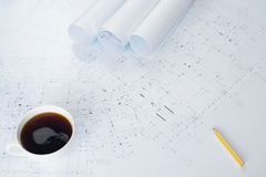 A cup of coffee and architectural plans on working table Royalty Free Stock Images