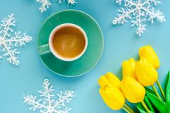 Cup of coffee with artificial yellow tulips and snowflake ornaments on blue background. For drinks and beverage in winter season concept stock photography