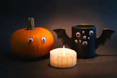 Cup of coffee as a bat for Halloween with eyes on  black background. Pumpkin   and  burning candle. Toy .  concept. Stock Photos