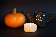 Cup of coffee as a bat for Halloween with eyes on  black background. Pumpkin   and  burning candle. Toy .  concept. Royalty Free Stock Images