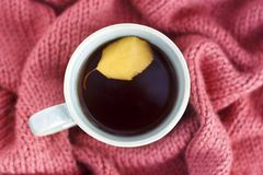 Cup of coffee with an autumn leaf on a knitted rug close-up, top view stock photo