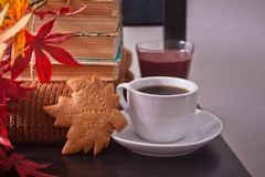 Cup of coffee, autumn leaves, cookies. old books on the wooden black chair. Autumn harvest. Autumn concept