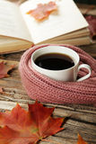 Cup of coffee with autumn leaves and a warm scarf on brown wooden background. Stock Photography