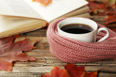 Cup of coffee with autumn leaves and a warm scarf on brown wooden background. Stock Photos