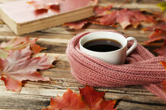 Cup of coffee with autumn leaves and a warm scarf on brown wooden background. Royalty Free Stock Photography