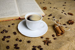 Cup of coffee on the background of burlap with a book. coffee beans . anise Stock Photo