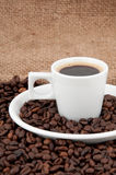 A cup of coffee on the background of coffee beans. Flavored coffee Royalty Free Stock Photos