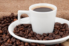 A cup of coffee on the background of coffee beans. Flavored coffee Stock Photos