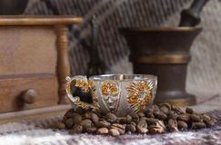 Cup of coffee on the background of coffee-mill. Coffee mill, cup and coffee beans Stock Image