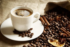 Cup of coffee with bag full of coffee,spices on linen Stock Image