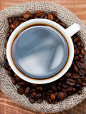 Cup of coffee in a bag of grains Royalty Free Stock Images