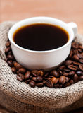 Cup of coffee in a bag of grains Stock Images