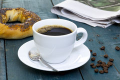 Cup of coffee with bagel and newspaper Royalty Free Stock Photography