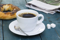 Cup of coffee with bagel and newspaper Royalty Free Stock Photos
