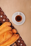 Cup of coffee and baguette on wooden table Royalty Free Stock Photography
