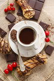 Cup of coffee, bar of chocolate and eclairs Royalty Free Stock Photo