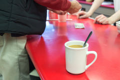 Cup of coffee on a bar table. A white cup of coffee with a spoon inside on a bar table inside a traditional american coffee shop, while a cutomer is paying his Stock Photography