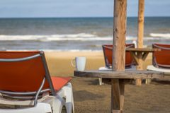 Cup of coffee on the beach of North Sea after rain. Orange sun loungers on the gold sand before sea on the North-sea beach.Cup of coffee on the beach after rain Stock Photo