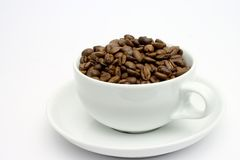Cup of coffee beans 1. Cappuccino cup filled with roasted beans,focus on beans Stock Photography