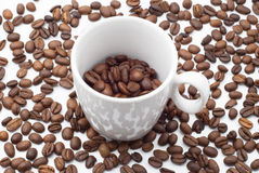 Cup of coffee beans. White coffee cup against the background of coffee beans Royalty Free Stock Image
