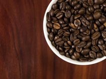 Cup with coffee beans. High angle view of coffee beans in a cup with a wooden background Royalty Free Stock Photos