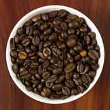 Cup with coffee beans. High angle view of coffee beans in a cup with a wooden background Royalty Free Stock Photography