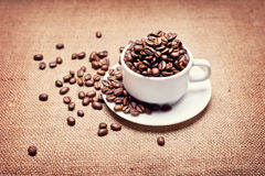Cup with coffee beans. On fabric texture background Stock Photo