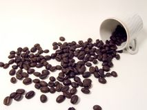 Cup and coffee beans. Coffee beans going out from a cup on a white background Royalty Free Stock Photography